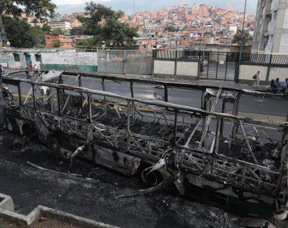 Vista de un autobús incendiado en la madrugada de este miércoles en Caracas. (Foto Prensa Libre: EFE)