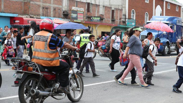 Ante la falta de una pasarela, niños y adultos se arriesgan al cruzar la carretera en el kilómetro 50 de la ruta Interamericana, El Tejar, Chimaltenango. (Foto Prensa Libre: César Pérez)