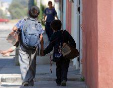 Dos hermanos caminan por la zona 3 de de Quetzaltenango mientras buscan clientes para lustrarles los zapatos.