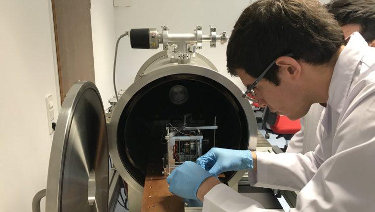 Emilio Miranda, del Equipo Proyecto CubeSat, prepara al aparato para que sea sometido a pruebas en la cámara de termovacío, en el laboratorio de la Universidad de Wurzburgo, en Alemania. (Foto Prensa Libre, Proyecto CubeSat).