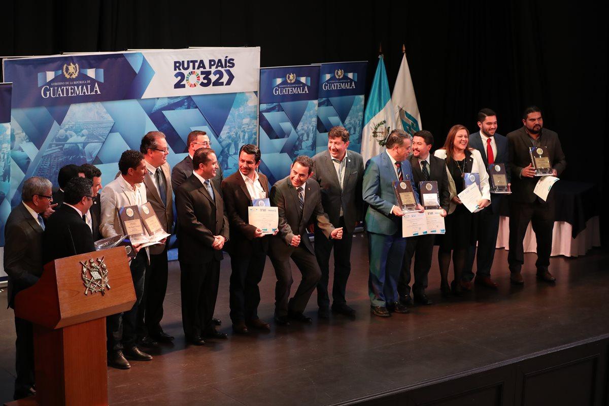 El presidente Jimmy Morales bromea con los alcaldes galardonados, durante la toma de la fotografía oficial del evento, en el Teatro de Don Juan, zona 1. (Foto Prensa Libre: E. García)