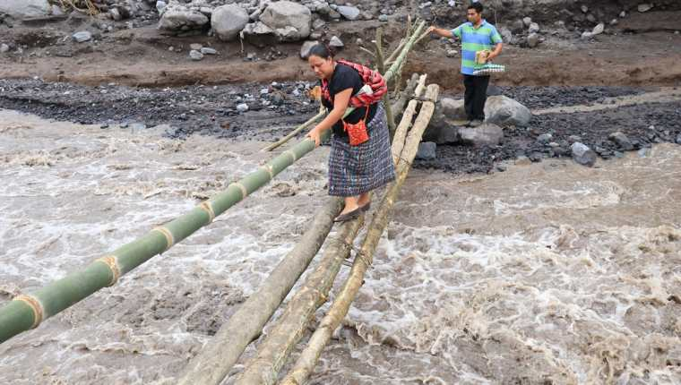 Mujer toma sus precauciones al momento de atravesar el paso provisional sobre el río Ceniza. (Foto Prensa Libre: Enrique Paredes).