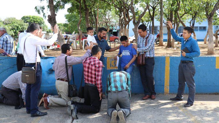 Un grupo de personas ora por el padre para que tenga fuerza, para superar la muerte de su hija. (Foto Prensa Libre: Mario Morales)