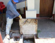Trabajador del Área de Salud muestra alcantarillado que permanece obstruido en el centro de Salud de la cabecera. (Foto Prensa Libre: Édgar Domínguez).