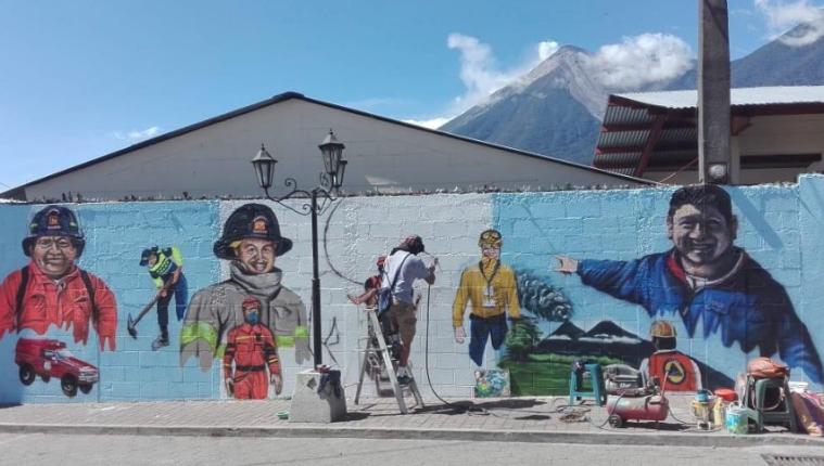 El mural recuerda a dos bomberos voluntarios y a Juan Galindo, delegado de la Conred, quienes murieron durante la erupción. (Foto Prensa Libre: Cortesía Denis David Sulecio).