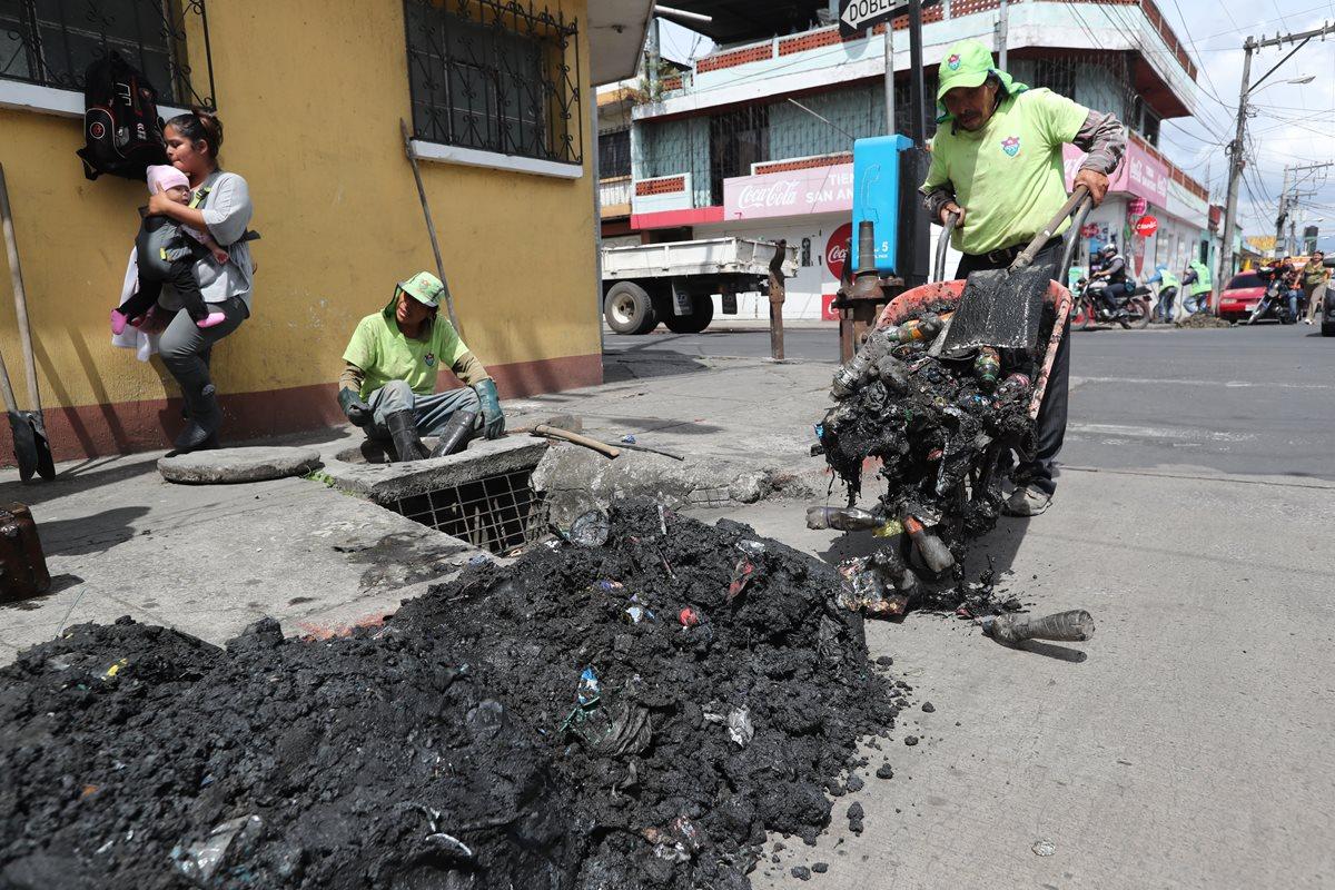 Empleados de la comuna capitalina extraen gran cantidad de desechos sólidos de una alcantarilla, en la zona 6. (Foto Prensa Libre: Érick Ávila)