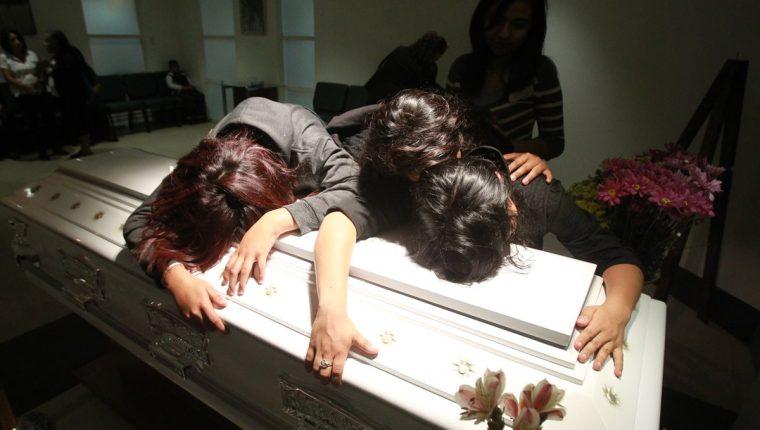 Familiares lloran sobre el ataúd de Brenda Dominguez, quien murió el sábado y fue inhumada el domingo. (Foto Prensa Libre: Estuardo Paredes)