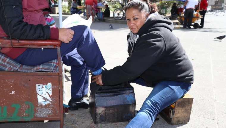 Ingrid Marisol Galindo Salguero lustra zapatos en el parque central de Quetzaltenango, actividad con la que lleva el sustento para sus tres hijos. (Foto Prensa Libre: María José Longo)