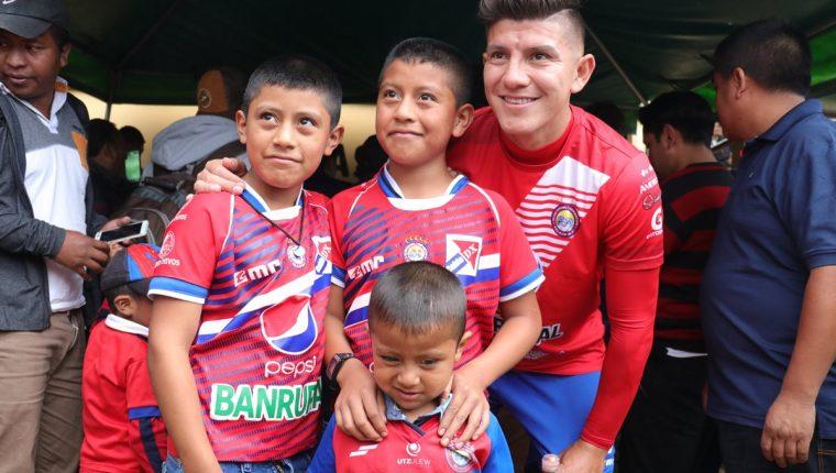 Kristian Guzmán, posa para una fotografía con niños que llegaron identificados con la camisola de Xelajú y quienes más disfrutaron del juego. (Foto Prensa Libre: Raúl Juárez)