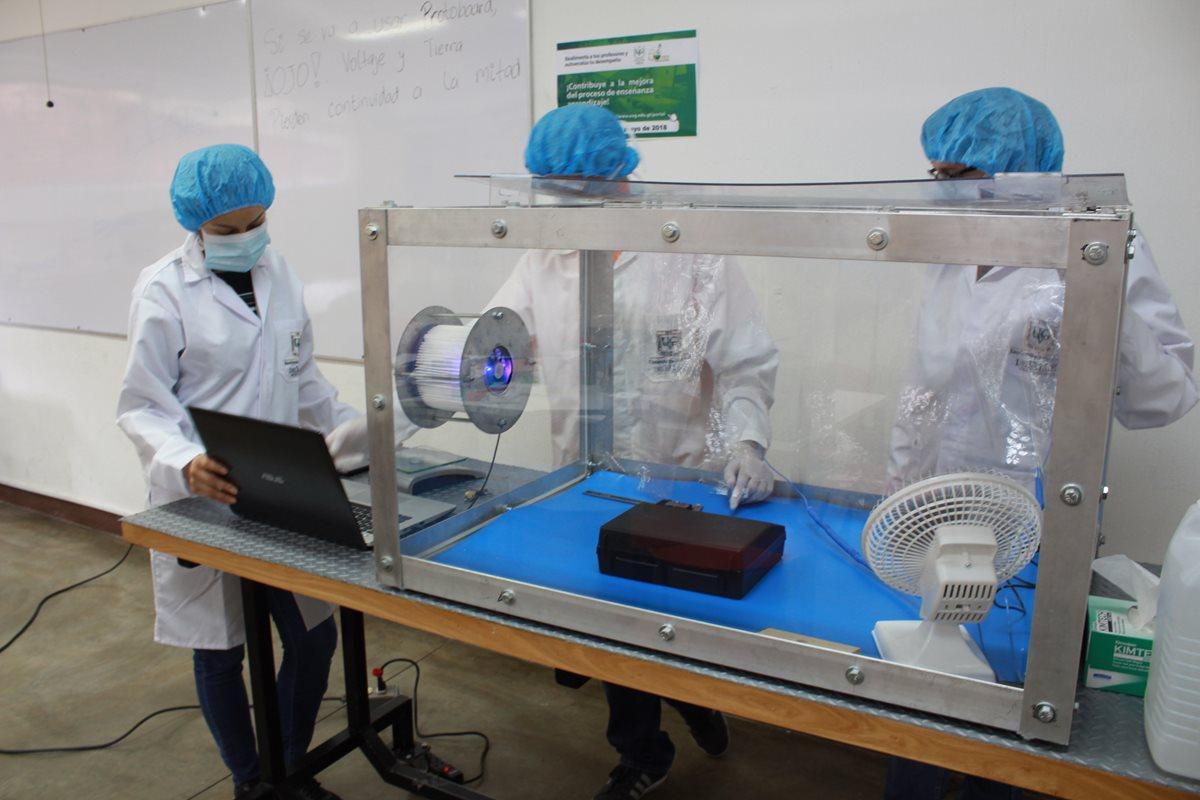Los estudiantes deben vestir equipo de protección personal cuando utilizan la caja limpia, para evitar que los componentes del CubeSat se impregnen de suciedad. (Foto Prensa Libre, Proyecto CubeSat)