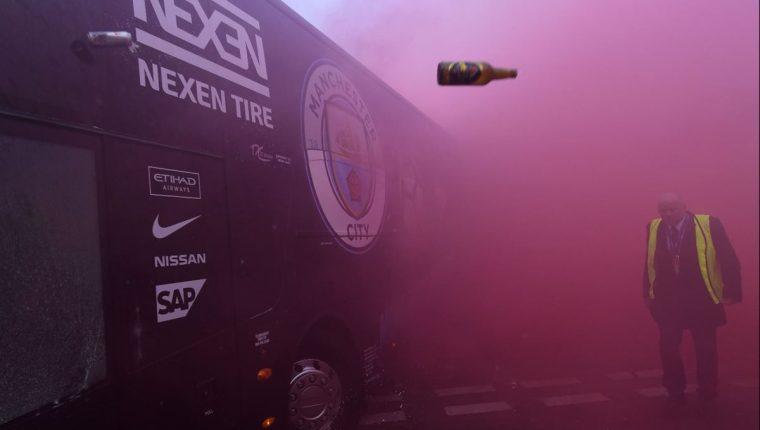 El bus del Mánchester City sufrió daños en su llegada al estadio del Liverpool por un grupo de aficionados. (Foto Prensa Libre: AFP).