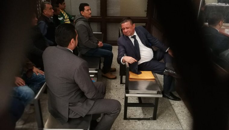Francisco Morales, alias chico dólar, conversa con otro de los sindicados en la carceleta del Tribunal. (Foto Prensa Libre: Óscar Rivas)