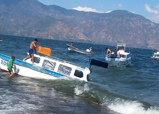 Lancha llega con dificultad a las playas del Lago de Atitlán, Sololá, debido a las condiciones climáticas que afectaron el lugar. (Foto Prensa Libre: Facebook Jaime Castro Galindo)