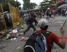 Migrantes hondureños se enfrentan a agentes de la Policía Nacional Civil quienes impiden el paso en la frontera entre Guatemala y México. (Foto Prensa Libre: EFE)