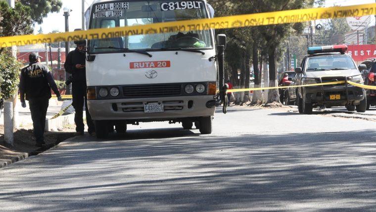 Investigadores del Ministerio Público revisan el bus de la ruta 20 donde esta mañana ocurrió un confuso incidente armado que dejó herido de bala al ayudante de unidad.. (Foto Prensa Libre: Mynor Toc)