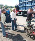 Una mujer enferma es llevada en hombros por su hijo, debido a bloqueos en ruta a suroccidente. (Foto Prensa Libre: Rolando Miranda)