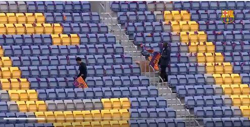 Trabajadores del Barcelona colocan banderas del equipo para hacer un mosaico al inicio del encuentro. (Foto Prensa Libre: Captura de pantalla Barcelona)