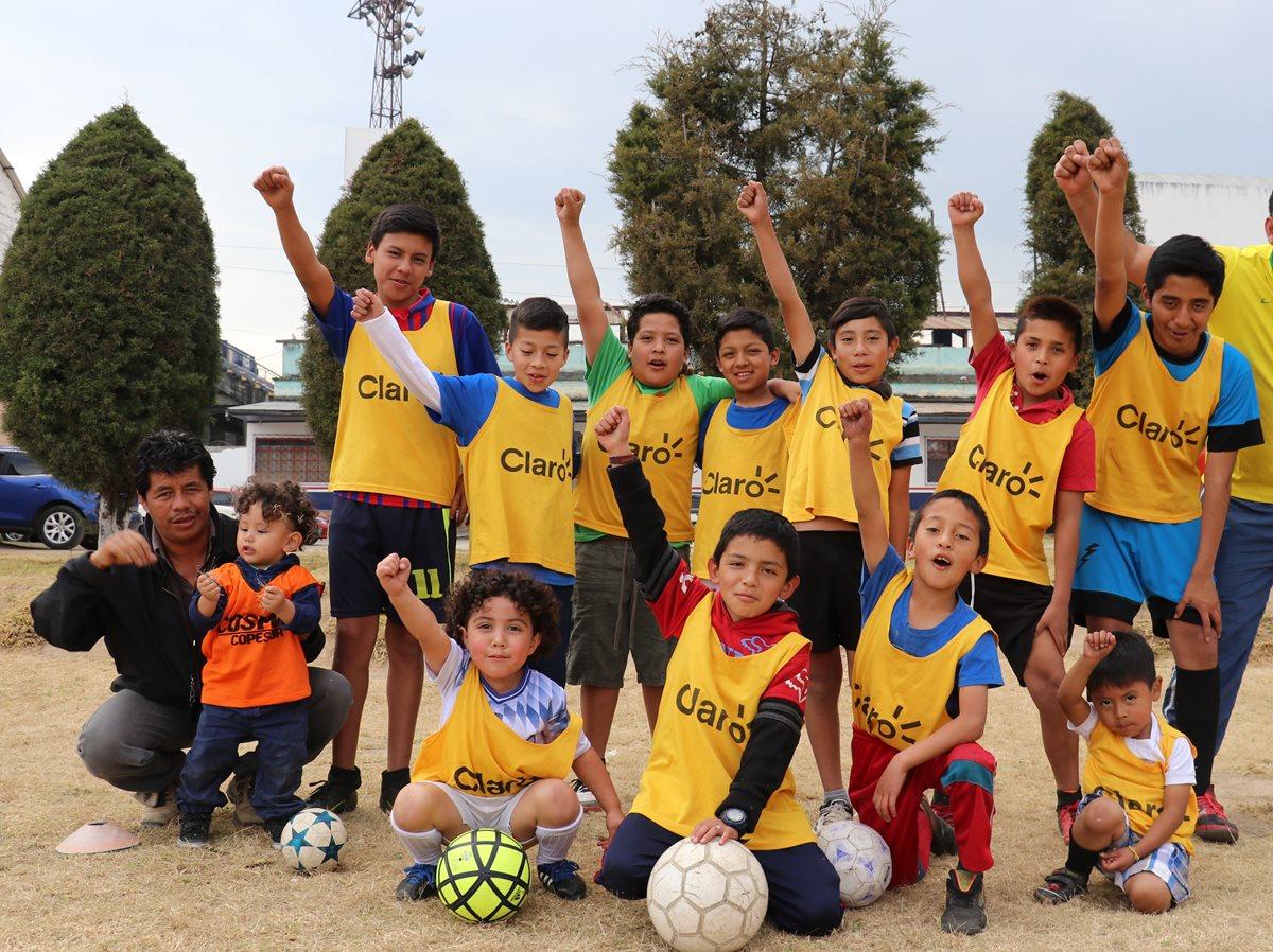 El entrenador Francisco Batres junto a algunos de los menores que practican futbol en la academia Cosmos Copesur. (Foto Prensa Libre: Raúl Juárez).