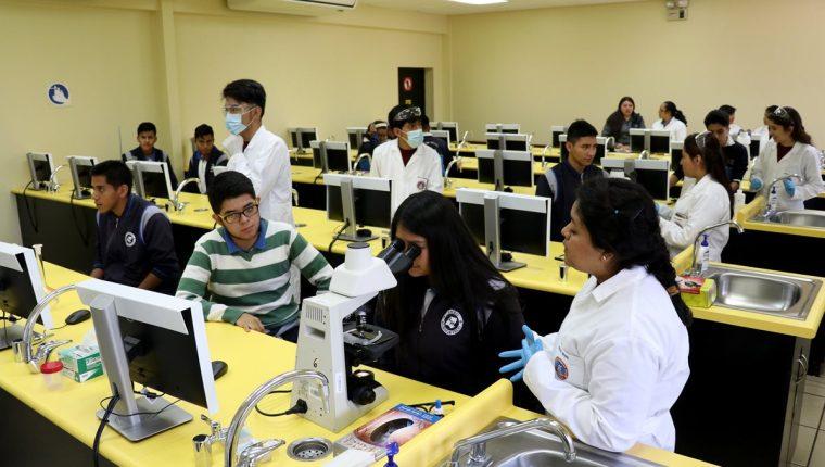 Estudiantes universitarios (de blanco) instruyen a un grupo de alumnos del nivel medio durante una feria académica efectuada en la sede de la Universidad Mariano Gálvez de Huehuetenango. (Foto Prensa Libre: Mike Castillo)