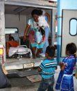 Los dos menores observan a su mamá, quien permanece en una camilla en la ambulancia, en Chiquimula. (Foto Prensa Libre: Mario Morales).