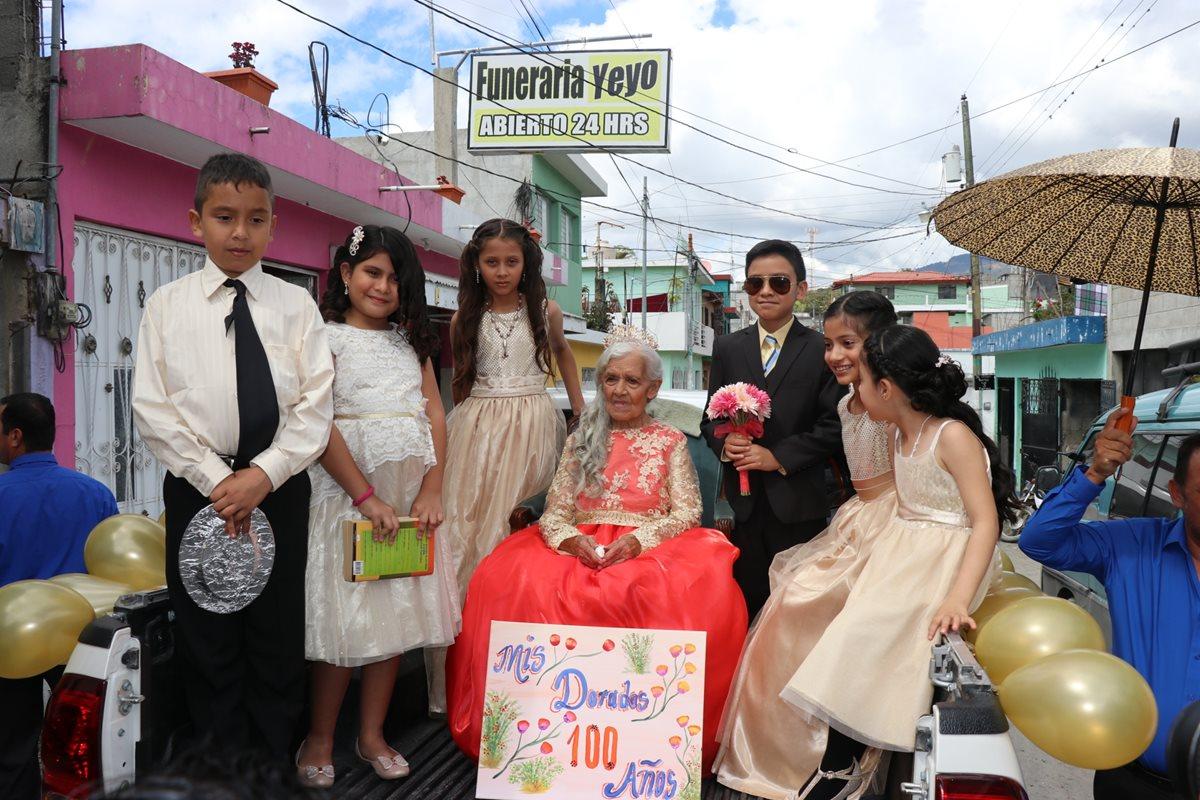Nietos y bisnietos acompañan a Juventina Rodríguez en la carroza en la que recorrió calles de Pachalum. (Foto Prensa Libre: Héctor Cordero)