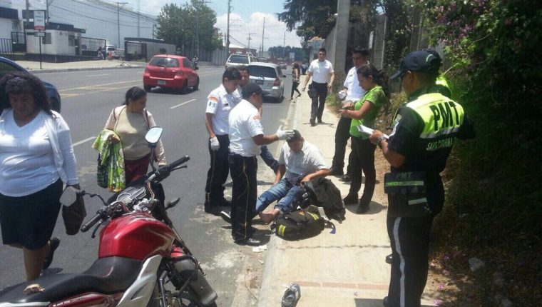 Bomberos Voluntarios atienden a un herido que viajaba en motocicleta después de un percance. (Foto Prensa Libre: CBV)
