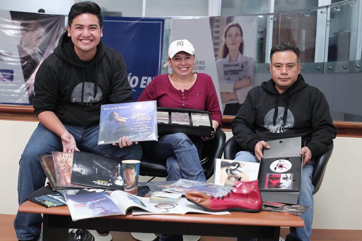 Marlon Quinto —20 años—, Anabella Reyes —48— y Mynor McKnight —46— muestran algunos de los artículos de su colección de objetos relacionados con Ricardo Arjona. (Foto Prensa Libre: Juan Diego González)