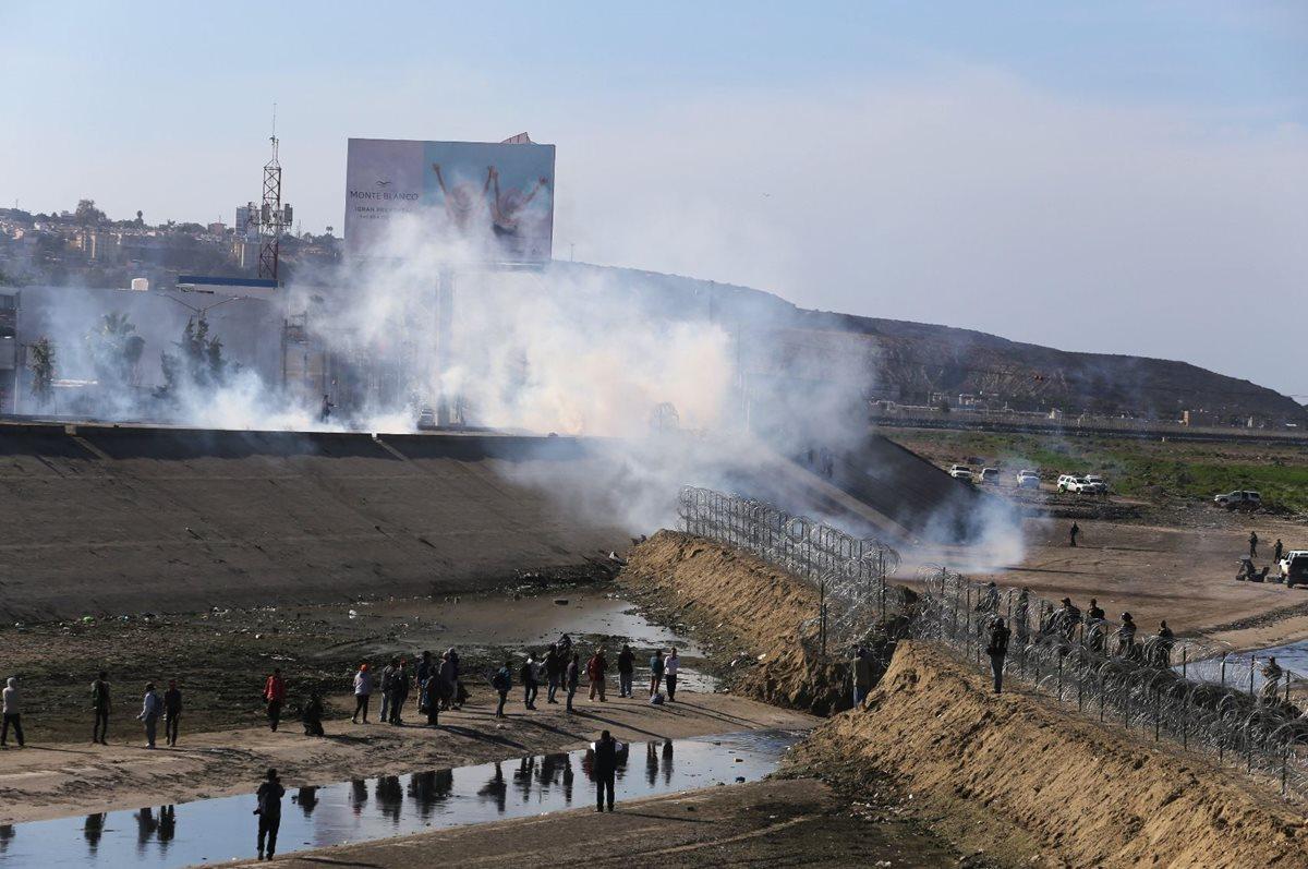 La fuerzas de seguridad lanzaron gas a los migrantes que intentaron cruzar por la fuerza. (Foto Prensa Libre: EFE)