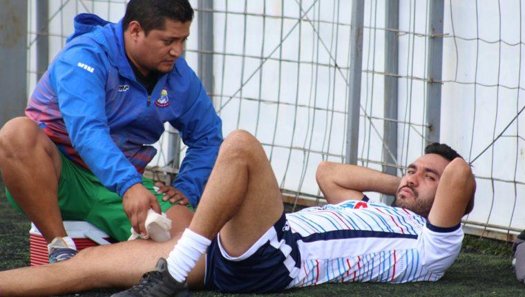 El fisioterapeuta de Xelajú, Henry Velásquez, realiza trabajo de masaje a Carlos Kamiani luego del trabajo de este jueves. (Foto Prensa Libre: Raúl Juárez)