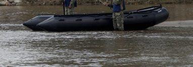 Integrantes de la Marina de México advierten por megáfonos a los hondureños que eviten cruzar. (Foto Prensa Libre: EFE)