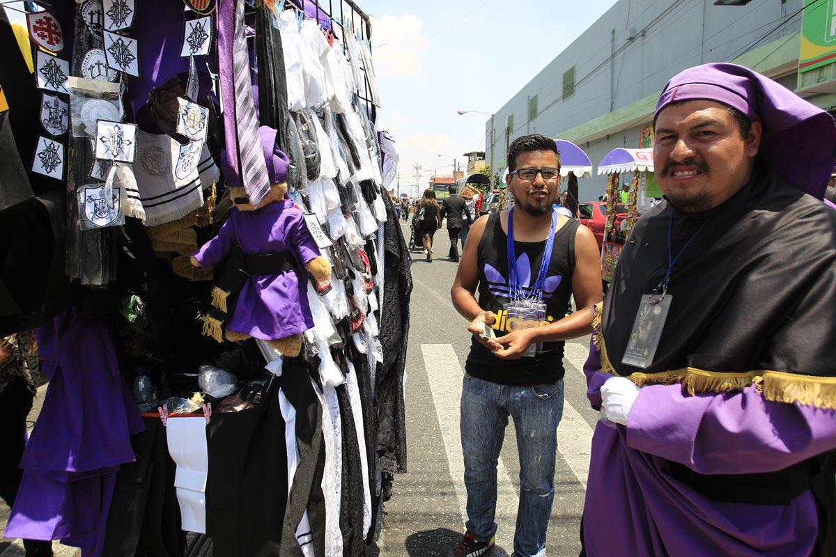 Ángel Rodrigo Mondragón ofrece sus productos a uno de los cucuruchos que participó en la procesión de Jesús de Las Tres Potencias de la Parroquia. (Foto Prensa Libre: Carlos Hernández).