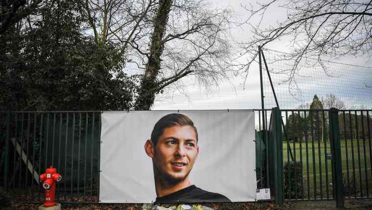 """Flowers and candles are left with the front page of French sports daily newspaper 'L'Equipe' reading """"The disappearance of a warrior"""" next to a portrait of Emiliano Sala in front of the entrance of the FC Nantes football club training center La Joneliere in La Chapelle-sur-Erdre on January 23, 2019, two days after the plane of Argentinian forward vanished during a flight from Nantes in western France to Cardiff in Wales. - The 28-year-old Argentine striker is one of two people still missing after contact was lost with the light aircraft he was travelling in on January 21, 2019 night. Sala was on his way to the Welsh capital to train with his new teammates for the first time after completing a £15 million ($19 million) move to Cardiff City from French side Nantes on January 19. (Photo by LOIC VENANCE / AFP)"""