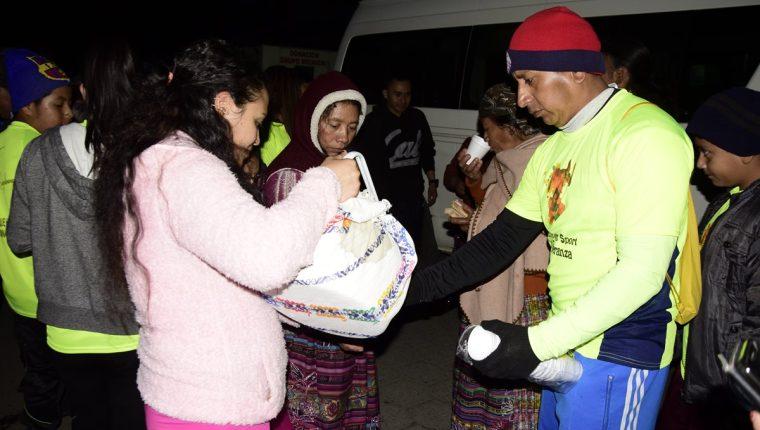 Los deportistas entregan café y pan a los familiares de los pacientes en el Hospital Regional de Quetzaltenango. (Foto Prensa Libre: Raúl Juárez)