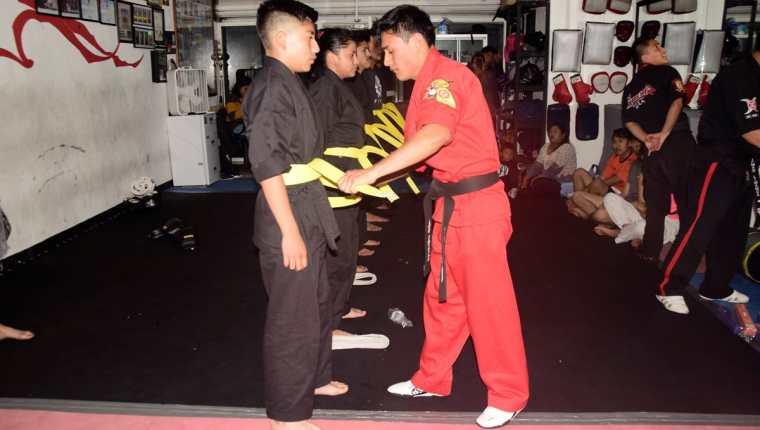 José Ixtacuy -derecha- gradúa a sus alumnos que hicieron cambios de cinta en las artes marciales. (Foto Prensa Libre: Raúl Juárez)
