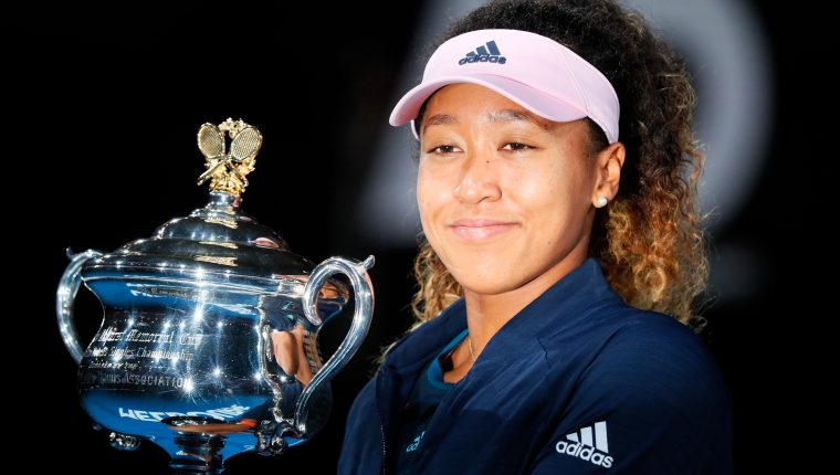 Japan's Naomi Osaka celebrates with the championship trophy during the presentation ceremony after her victory against Czech Republic's Petra Kvitova in the women's singles final on day 13 of the Australian Open tennis tournament in Melbourne on January 26, 2019. (Photo by DAVID GRAY / AFP) / -- IMAGE RESTRICTED TO EDITORIAL USE - STRICTLY NO COMMERCIAL USE --