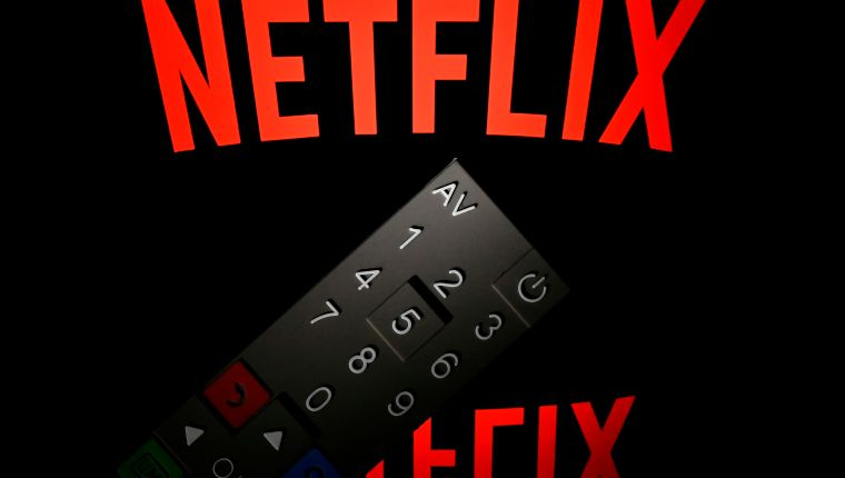 (FILES)This illustration picture taken on April 21, 2018 in Paris shows the logo of the Netflix entertainment company, displayed on a tablet screen with a remote control in front of it. - Netflix unveiled plans January 15, 2019 to boost prices for US subscribers, a move that helped lift shares of the streaming television giant which now faces an array of new competitors.The California-based company, which has nearly half of its 130 million paid members in the US, will raise the price of its most popular streaming plan with high-definition video by 18 percent to $12.99 per month. (Photo by Lionel BONAVENTURE / AFP)