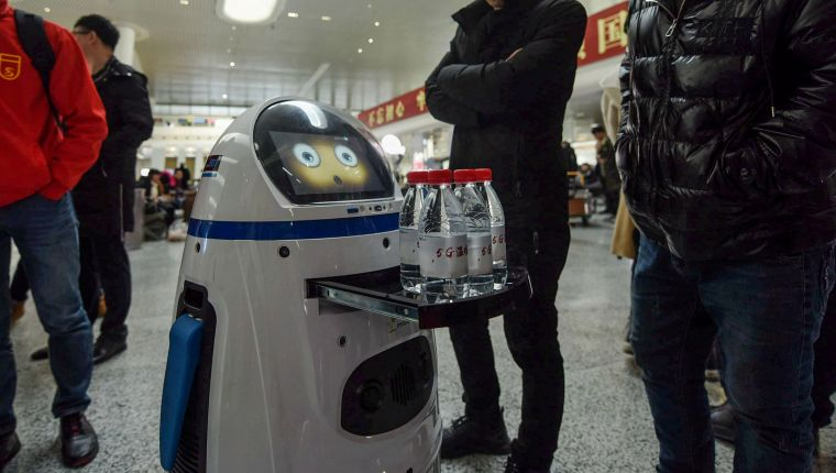 A 5G service robot serves free bottles of water to travellers at East Railway Station in Hangzhou in China's eastern Zhejiang province on January 21, 2019, the first day of the Spring Festival travel rush. (Photo by STR / AFP) / China OUT