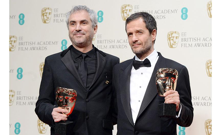 El director mejicano Alfonso Cuarón y el productor británico David Heyman juntos tras recibir los premios por la película Roma.  (Foto Prensa Libre, EFE)