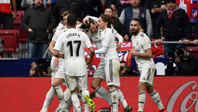 Real Madrid's Welsh forward Gareth Bale (C) celebrates with teammates after scoring during the Spanish league football match Club Atletico de Madrid against Real Madrid CF at the Wanda Metropolitano stadium in Madrid on February 9, 2019. (Photo by PIERRE-PHILIPPE MARCOU / AFP)