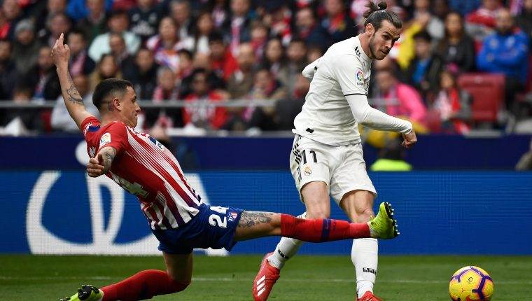 Real Madrid's Welsh forward Gareth Bale (R) scores next to Atletico Madrid's Uruguayan defender Jose Gimenez during the Spanish league football match Club Atletico de Madrid against Real Madrid CF at the Wanda Metropolitano stadium in Madrid on February 9, 2019. (Photo by PIERRE-PHILIPPE MARCOU / AFP)