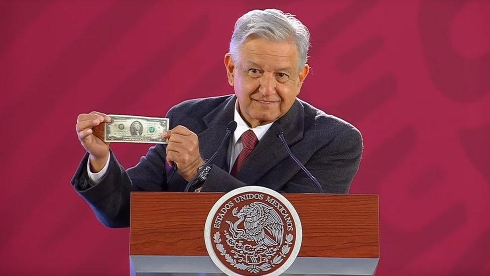 AMLO guarda un billete de dos dólares en su cartera.