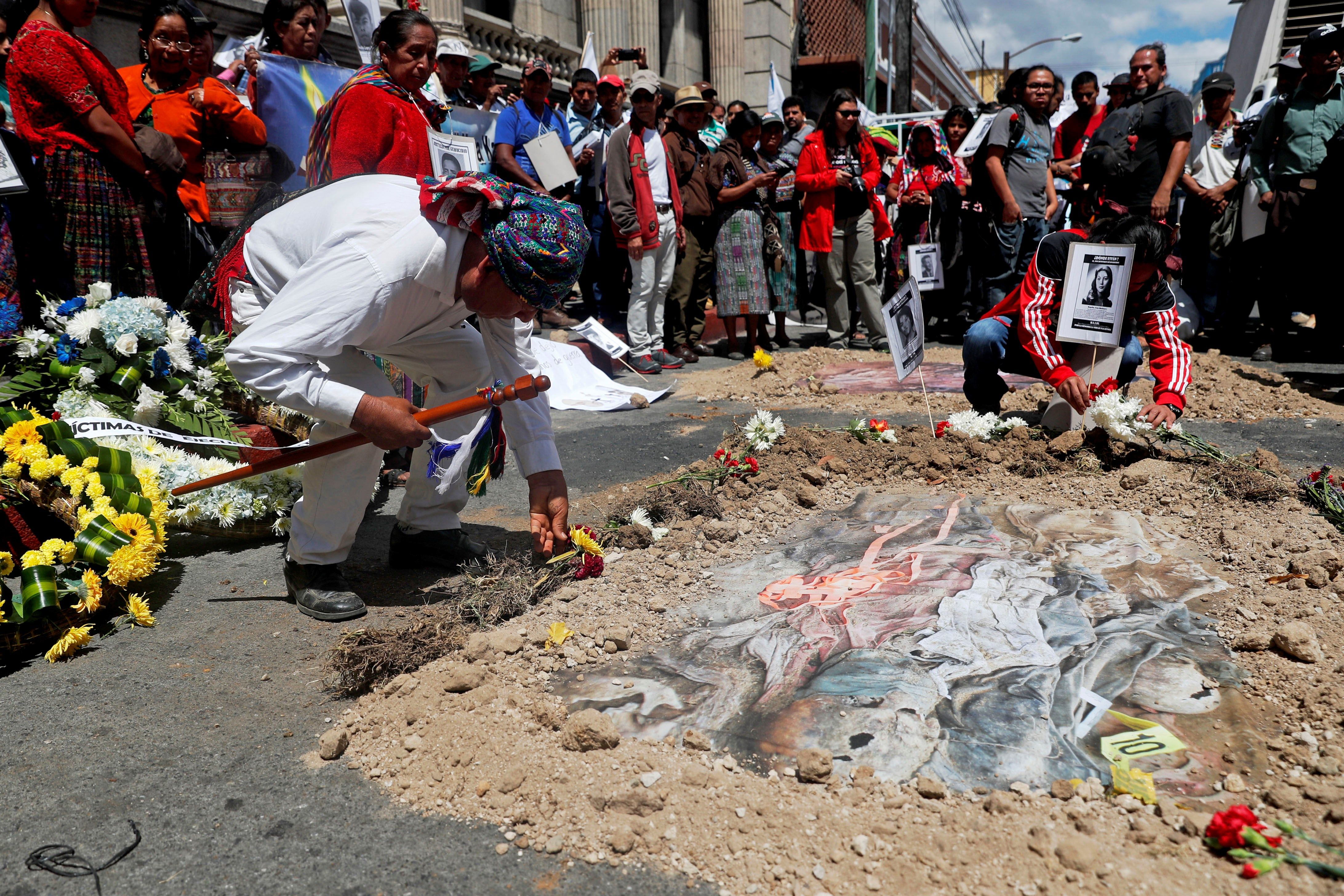 GU1001. CIUDAD DE GUATEMALA (GUATEMALA), 25/02/2019.- Un hombre coloca una flor frente a la simulación de una fosa común durante una manifestación con fotografías de familiares muertos o desaparecidos durante la guerra interna, este lunes, frente al Congreso, en Ciudad de Guatemala (Guatemala). Familiares y víctimas de la guerra interna (1960-1996) exigieron este lunes que se enjuicie y castigue a los responsables del genocidio en Guatemala, y rechazaron las intenciones del Congreso de favorecerlos con una amnistía general a través de una reforma a la Ley de Reconciliación Nacional. Durante la protesta, decenas de familiares y víctimas del conflicto enfilaron hacia la Plaza de la Constitución y luego al Congreso para exigir a los diputados que se abstengan de aprobar las reformas a dicha ley. EFE/Esteban Biba