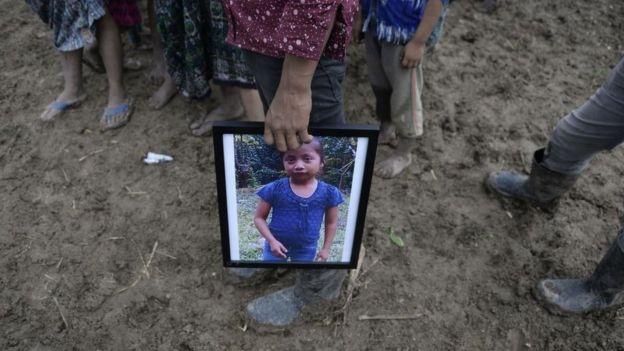 Un familiar de Jakelin Caal sostiene la fotografía de la niña durante su sepelio. (Foto Prensa Libre: Hemeroteca PL)