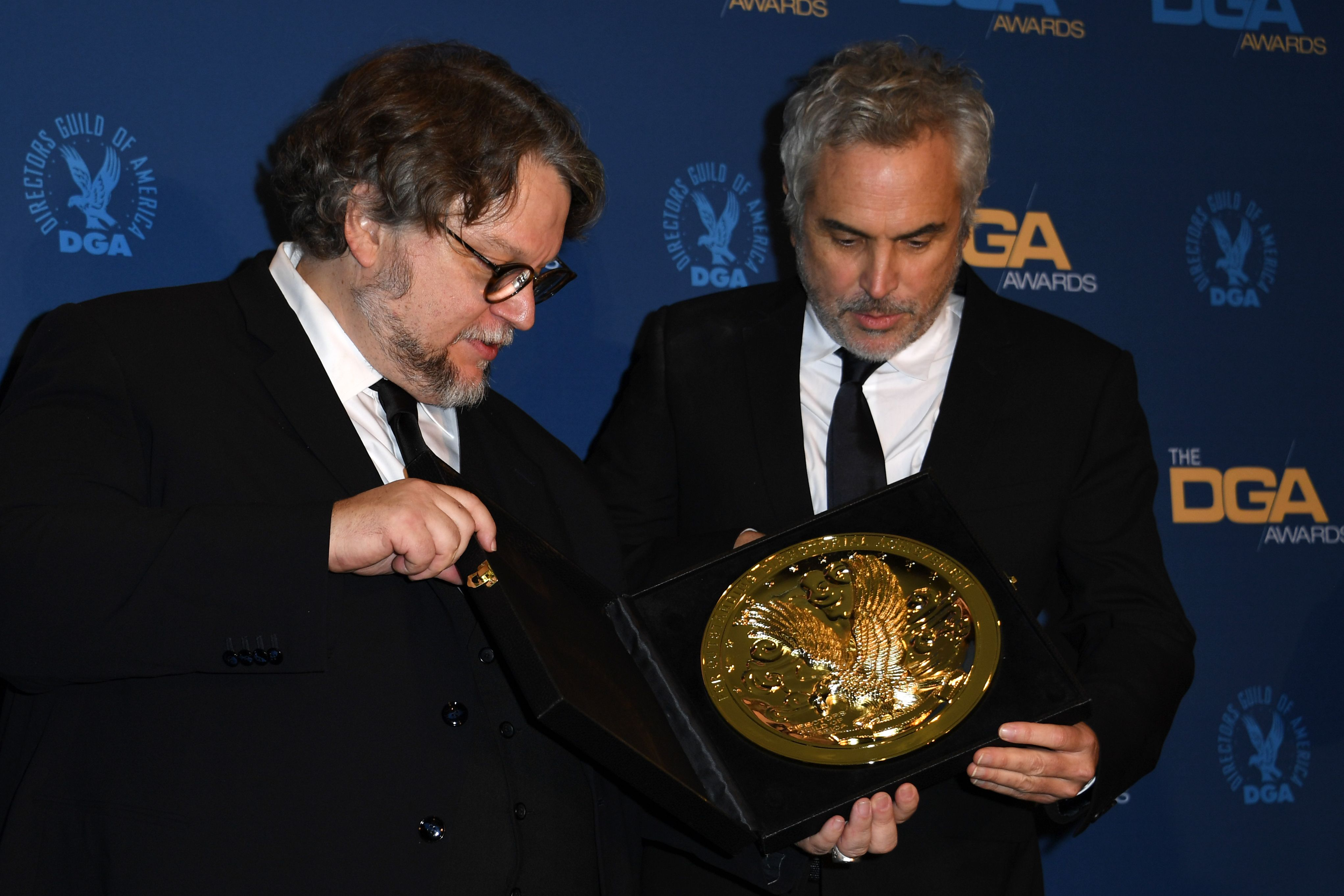 """Director Alfonso Cuaron (R) poses next to director Guillermo Del Toro with the award for Outstanding Directorial Achievement in Feature Film for """"Roma"""" in the press room during the 71st Annual Directors Guild Of America (DGA) Awards at the Ray Dolby Ballroom in Hollywood on February 2, 2019. (Photo by Valerie MACON / AFP)"""