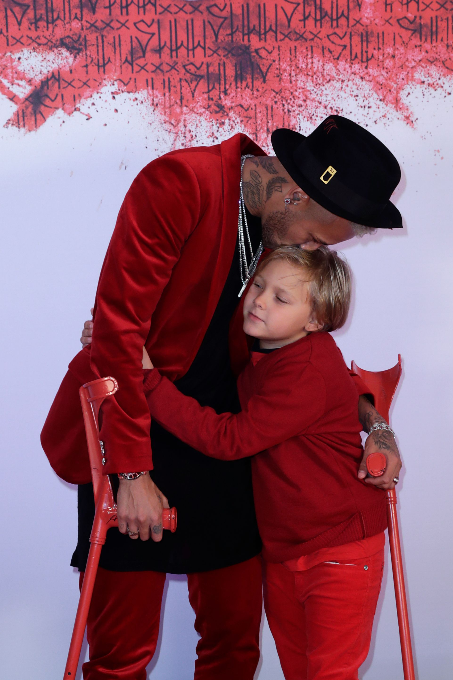 Paris Saint-Germain's Brazilian forward Neymar (L) kisses his son Davi Lucca as he arrives at his birthday party in Paris on February 4, 2019. (Photo by Thomas SAMSON / AFP)