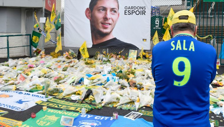 A supporter stands in front of flowers placed in front of a giant portrait of Argentinian former Nantes' forward Emilianio Sala outside La Beaujoire stadium before the French Cup football match between FC Nantes and Toulouse FC in Nantes on February 5, 2019. (Photo by Sebastien SALOM-GOMIS / AFP)