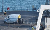 Police forensics and a coroners vehicle stand parked by the Geo Ocean III, transporting a body recovered from the wreckage of a plane carrying Argentine footballer Emiliano Sala is docked in Weymouth harbour, south west England on February 7, 2019. - Investigators recovered a body in the Channel and transported it to Britain today for identification. (Photo by Glyn KIRK / AFP)
