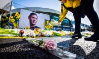A FC Nantes supporter puts yellow flowers in front of the portrait of late Argentinian forward Emiliano Sala prior to the French L1 football match between FC Nantes and Nimes Olympique at the La Beaujoire stadium in Nantes, western France on February 10, 2019. - FC Nantes football club announced on February 8, 2019 that it will freeze the #9 jersey as a tribute to Cardiff City and former Nantes footballer Emiliano Sala who died in a plane crash in the English Channel on January 21, 2019. (Photo by LOIC VENANCE / AFP)