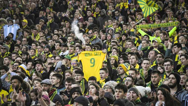 "A FC Nantes supporter holds a #9 jersey reading ""Thank you Sala"" in memory of late Argentinian forward Emiliano Sala prior to the French L1 football match between FC Nantes and Nimes Olympique at the La Beaujoire stadium in Nantes, western France on February 10, 2019. - FC Nantes football club announced on February 8, 2019 that it will freeze the #9 jersey as a tribute to Cardiff City and former Nantes footballer Emiliano Sala who died in a plane crash in the English Channel on January 21, 2019. (Photo by LOIC VENANCE / AFP)"