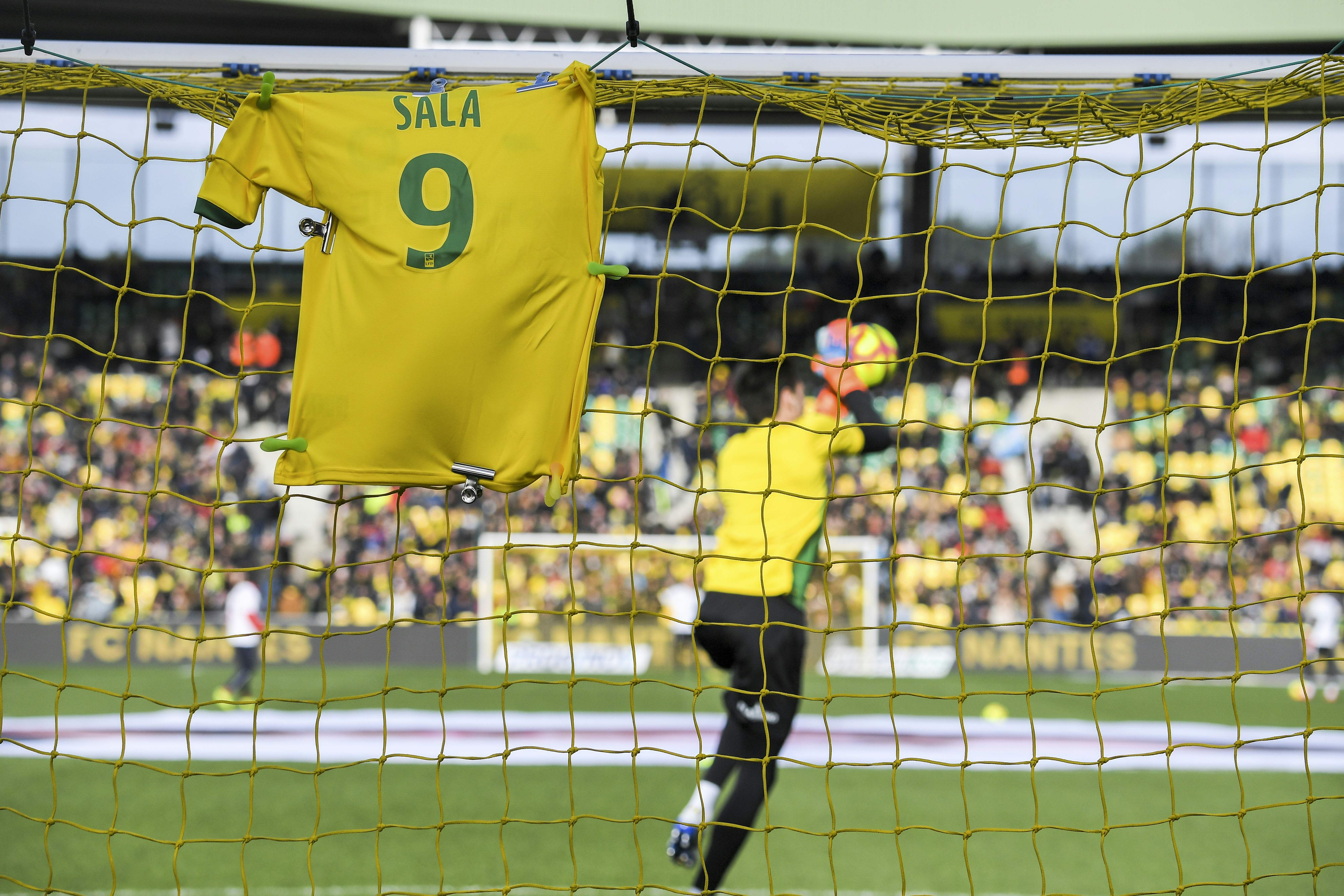 A #9 jersey is displayed on the goal in memory of late Argentinian forward Emiliano Sala prior to the French L1 football match between FC Nantes and Nimes Olympique at the La Beaujoire stadium in Nantes, western France on February 10, 2019. - FC Nantes football club announced on February 8, 2019 that it will freeze the #9 jersey as a tribute to Cardiff City and former Nantes footballer Emiliano Sala who died in a plane crash in the English Channel on January 21, 2019. (Photo by LOIC VENANCE / AFP)